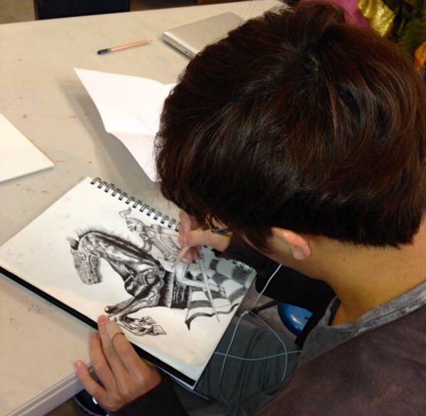 Min Lee works on the drawing that will be featured on the cover of the upcoming musical production.