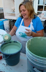 Pre-K teacher Linda Gartrell applies glaze to a mug she made.
