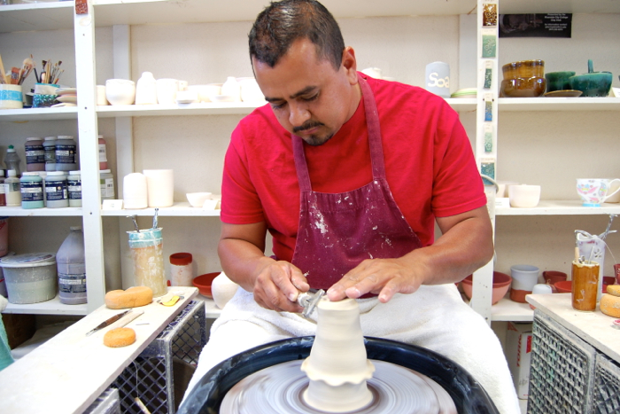 Kitchen staff member Moises Ferrel works on the wheel. He says the evening ceramics sessions are like therapy to him.