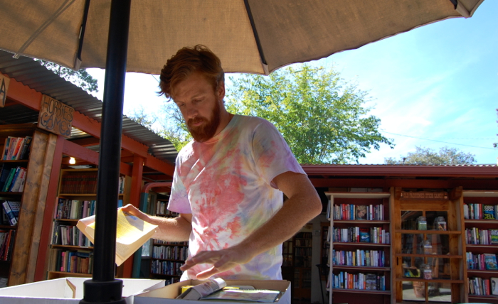 Librarian Casey Brough sifts through books to add to the OVS library at Bar's Books in downtown Ojai -- Photo by Daphne Psaledakis