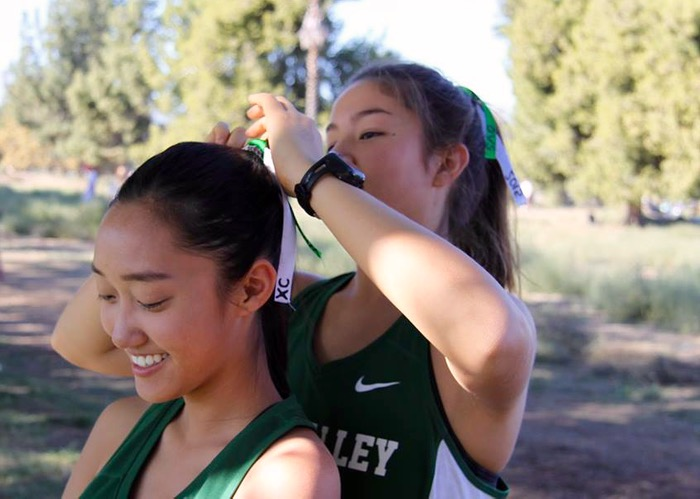 Senior captain Ally Feiss helps teammate Winnie Chang prepare for the race -- Photo by Momoe Takamatsu