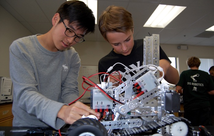 Robotics team members Minwoo Sohn and Philp Trompke put last minute touches on their robot before Saturday's competition -- Photo by Fred Alvarez