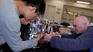 Senior Minwoo Sohn and robotics teacher Chris Wescott work on the final steps to robot construction the day before the team's first competition -- Photo by Fred Alvarez