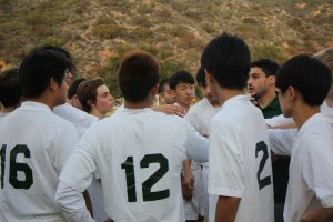 Soccer coach Hunter Helman gives his team a half-time pep talk during a recent game -- Photo by Minwoo Sohn