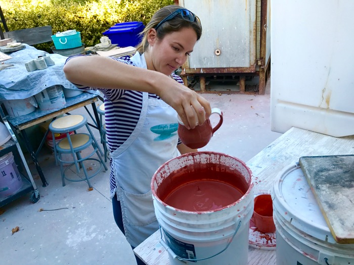 Equestrian instructor Krista Belgum glazes one of the many pieces she has thrown -- Photo By Fred Alvarez