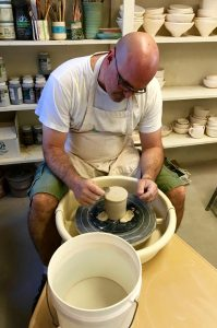 Robotics teacher Chris Westcott trims excess clay from a stein he has thrown -- Photo by Fred Alvarez
