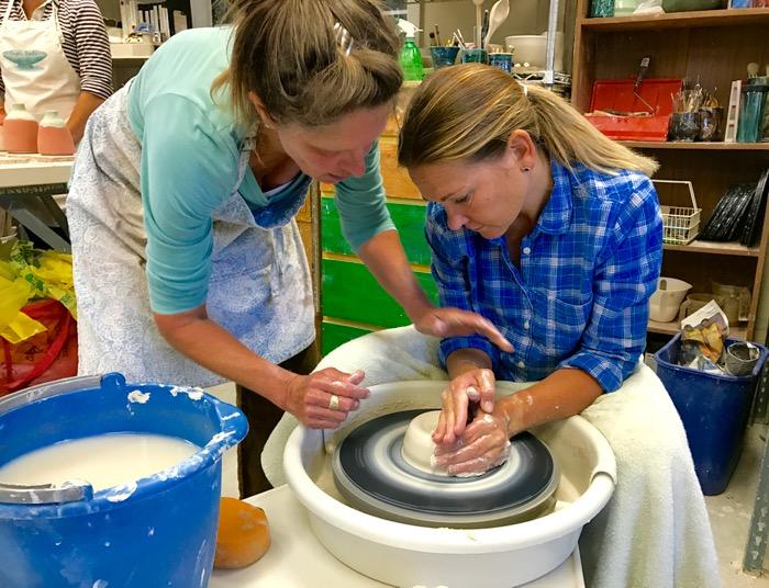 Master ceramicist Jody Cooper teaches Spanish teacher Gretchen Stevens how to center clay -- Photo by Fred Alvarez