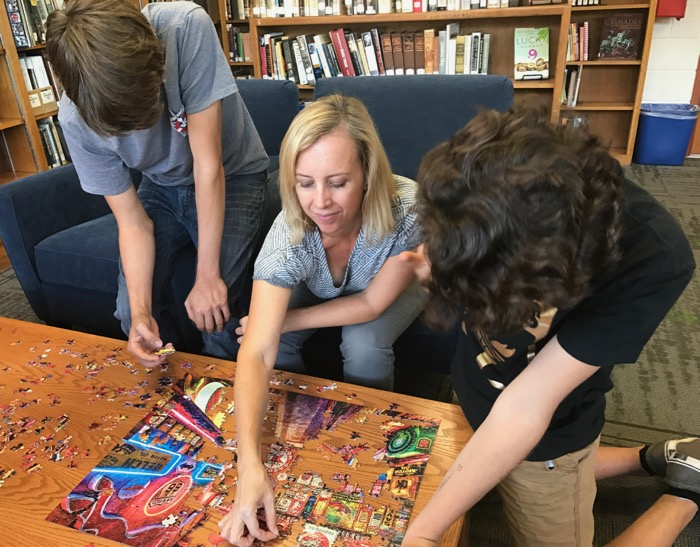 Jacob Tadlock (far left) and Shea Colborn tackle the latest puzzle with Mrs. Nishiya as part of Puzzle Club -- Photo by Fred Alvarez