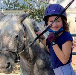 Lower campus rider spending time with her pony.